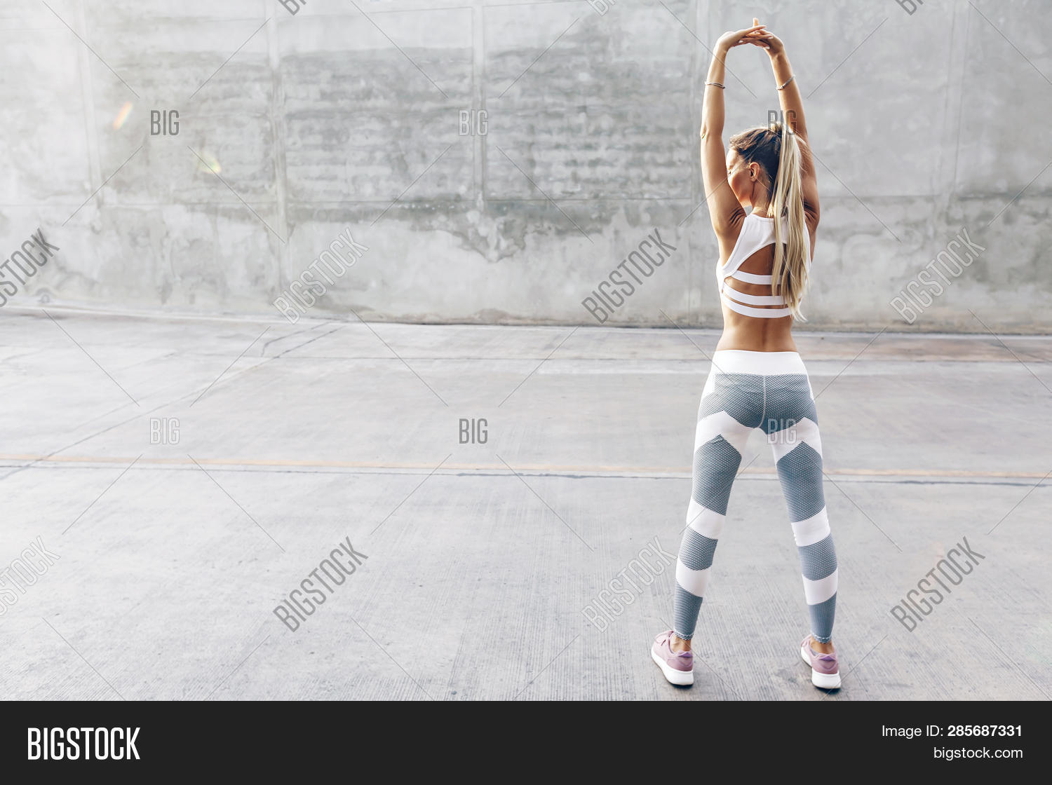 Fitness woman in sportswear doing stretching exercise on the city street over gray concrete backgrou