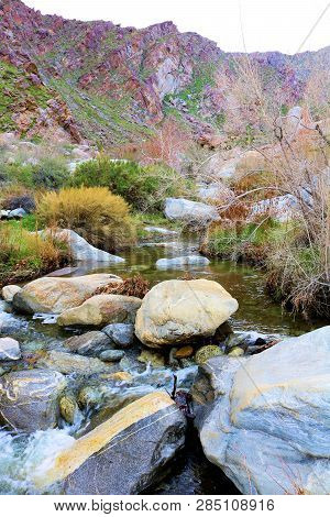 Creek surrounded by chaparral shrubs and sage plants on an arid plain besides barren mountains taken at Tahquitz Canyon in Palm Springs, CA stock photo