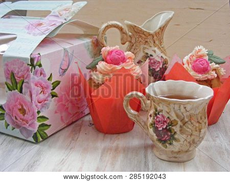 Afternoon tea served with a flower cupcakes and vintage teacup on shabby background stock photo