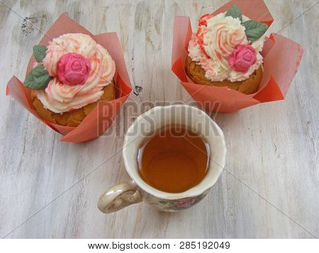 Afternoon tea with roses cupcakes in vintage teacup on shabby table flat wiev stock photo