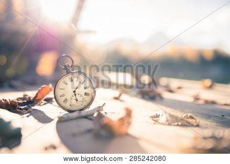 Hand held stop watch outdoors, autumn, blurry blue lake in the background stock photo
