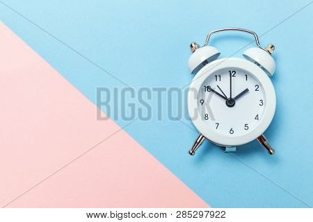 Ringing twin bell vintage classic alarm clock Isolated on blue pink pastel colorful trendy background. Rest hours time of life good morning night wake up awake concept. Flat lay top view copy space stock photo