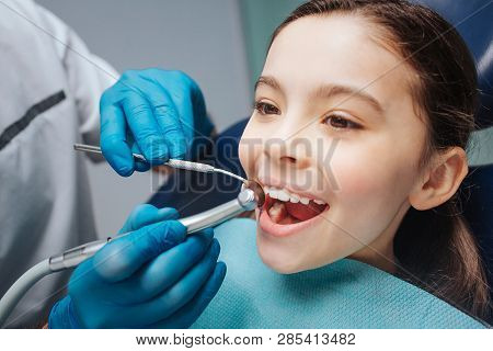 Happy girl sit in dentist chair. She keep mouth opened. Dentist use drill and another dental tool. Kid show front teeth. stock photo