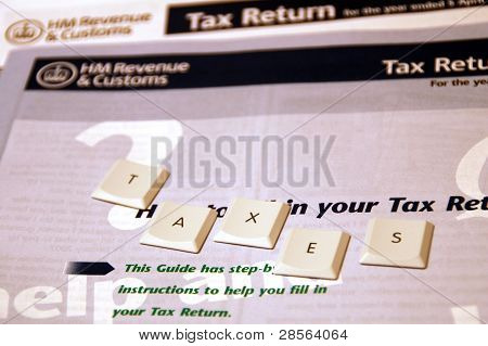 Taxes spelt out using keyboard letters on a UK tax return form background ** Note: Shallow depth of field stock photo