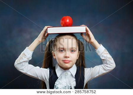 Cute Schoolgirl Hold Book Apple On Head Portrait. Calm Adorable Young Girl With Two Ponytail Look At