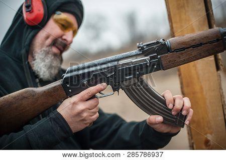 Close-up detail view of kalashnikov riffle machine gun cartridge bullet clip reloading. Load and unload ak47 stock photo