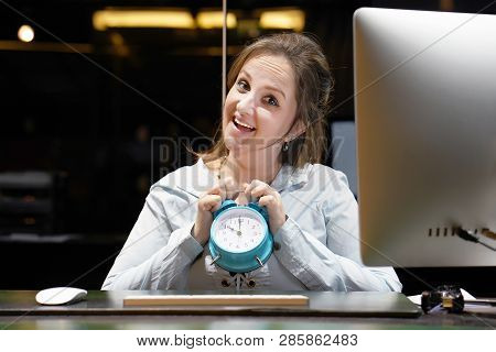Hotel administrator. A woman-reception worker holds an alarm clock in her hand in the workplace. Profile shot of attractive executives at the reception of a hotel. Woman holding a clock. stock photo