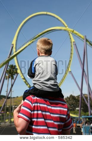 A boy on his fathers back going to ride the roller coaster stock photo
