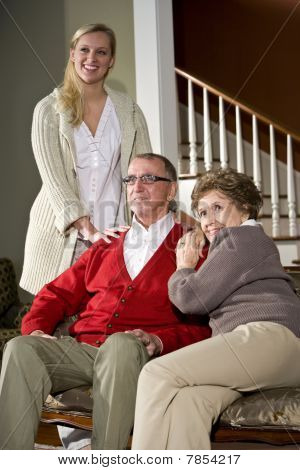 Senior couple on couch at home with adult daughter stock photo