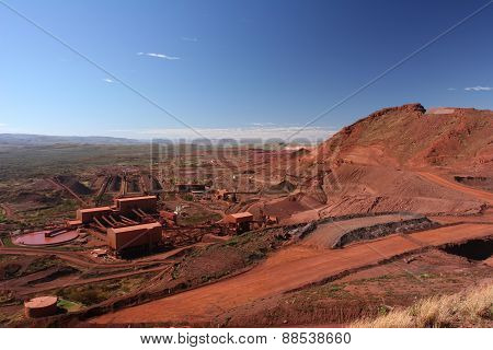 Iron ore mining operations near Tom Price in the Pilbara region of Western Australia under a blue sky with dark red ore rich soils stock photo