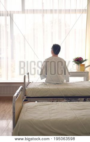 Rear view of a male patient sitting in hospital bed stock photo