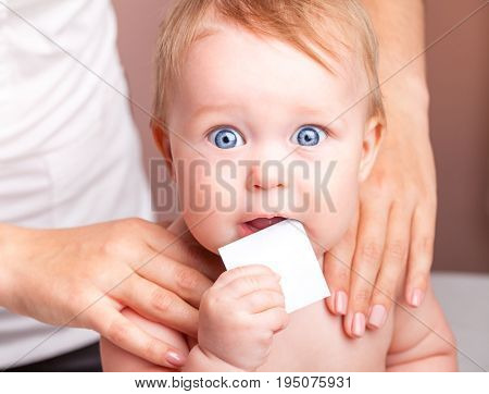 Seven month baby girl's shoulder joints being manipulated by an osteopath, an alternative medicine treatment. Child is holding blank card in mouth looking at camera stock photo