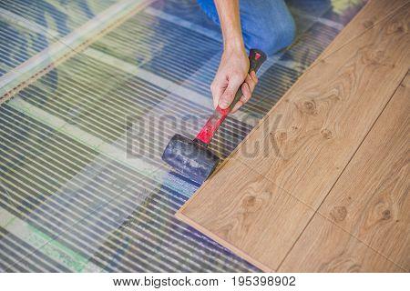 Man installing new wooden laminate flooring on a warm film floor. infrared floor heating system under laminate floor stock photo