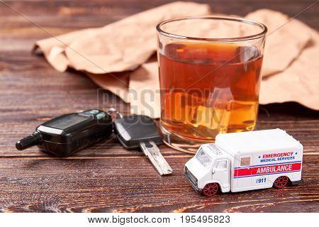 Alcohol, keys, ambulance, wooden background. Glass of whiskey, keys, car ambulance. Drinking alcohol beverage and hospitalization by emergency ambulance. stock photo