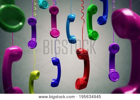 Red and multi-coloured telephone receiver hanging over gray background concept for on the phone, cus