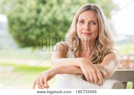 Happy senior woman relaxing on bench in the lawn. Close up face of a mature blonde woman smiling and