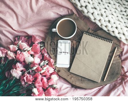 Wooden tray with paper sketchbook, smartphone and spring flowers on pink bedding. Relaxing, or working, or writing diary or blog in bed at home. stock photo