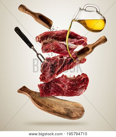Flying pieces of raw steaks, with ingredients for cooking, served on woodenboard. Concept of food preparation in low gravity mode. Separated on smooth background. High resolution image stock photo