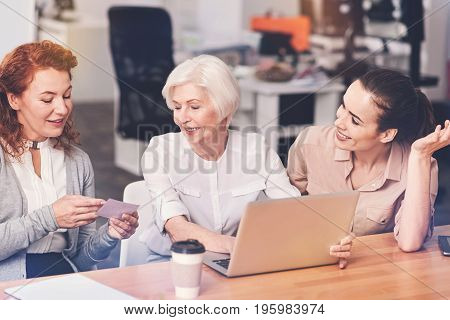 Collecting new information. Hardworking dedicated active colleagues sharing the updates of their project with their chef while showing her their development and being enthusiastic about it stock photo