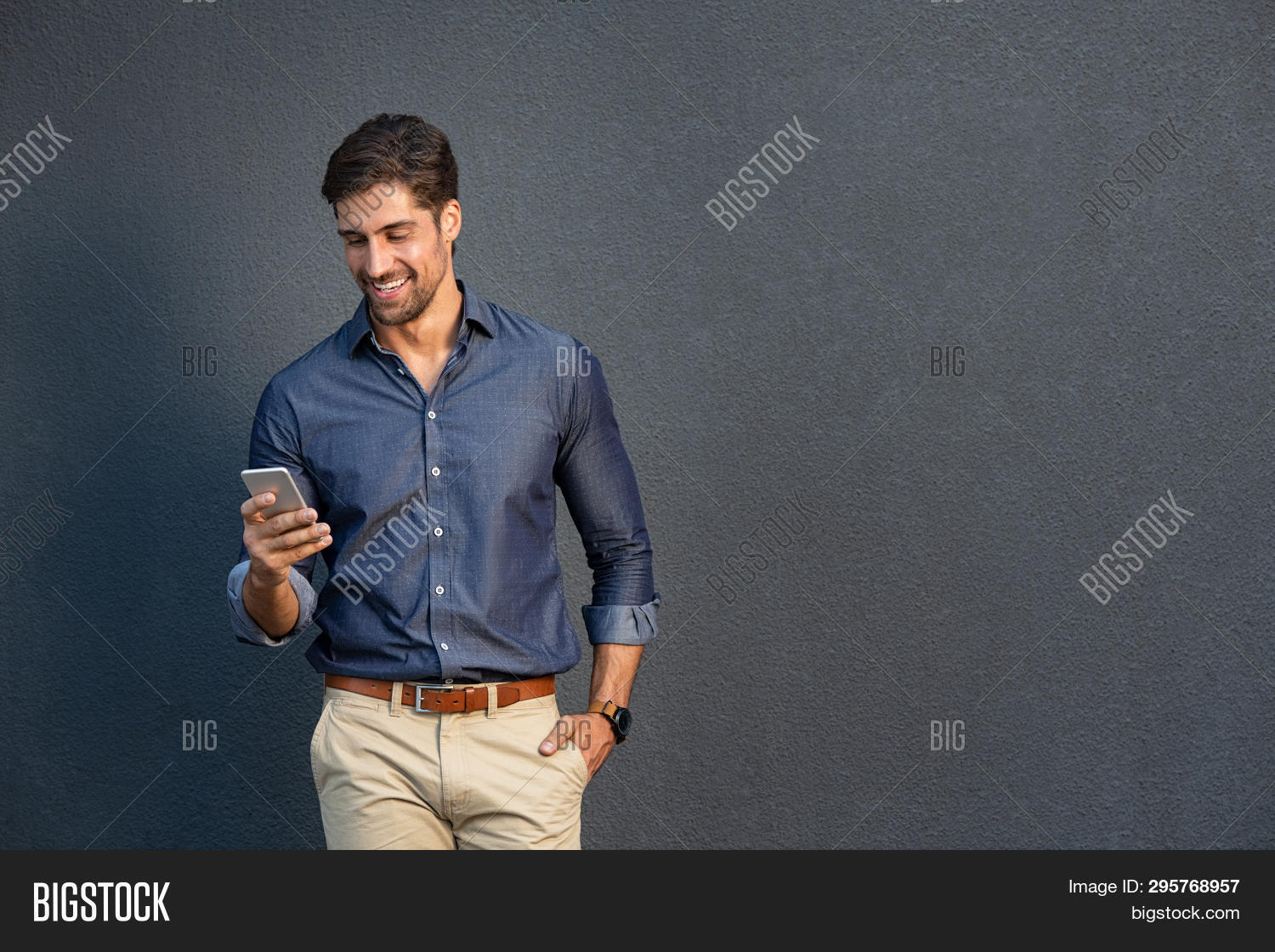 Portrait of young man leaning against a grey wall using mobile phone. Happy business man messaging w