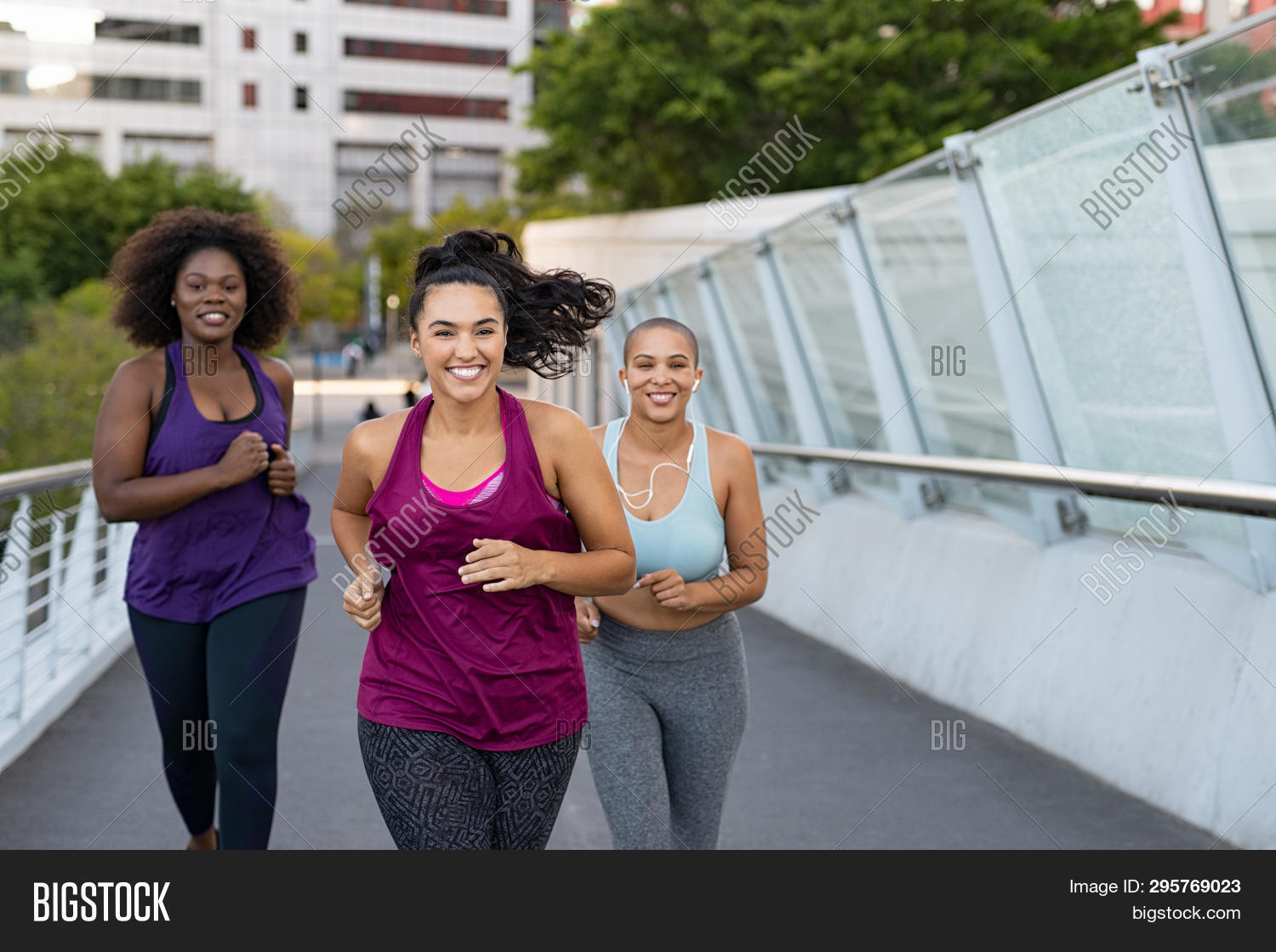 Happy young curvy women jogging together on city bridge. Healthy girls friends running on the city s
