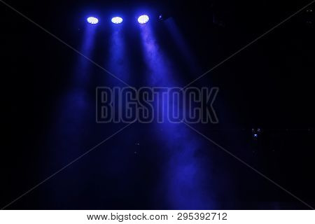 Stage lights. Several projectors in the dark. Multi-colored light beams from the stage spotlights on the stage in the smoke at the time of the entertainment show. Night club. Lights show. Lazer show stock photo