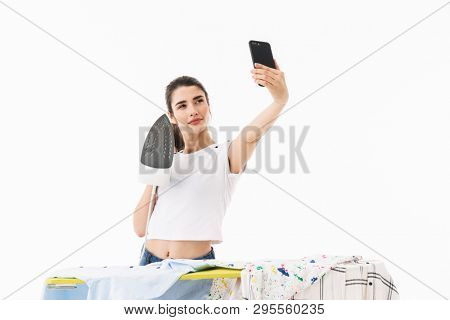 Photo of optimistic woman housewife 20s dressed in casual wear holding mobile phone and taking selfie photo while ironing clean clothes on board isolated over white background stock photo