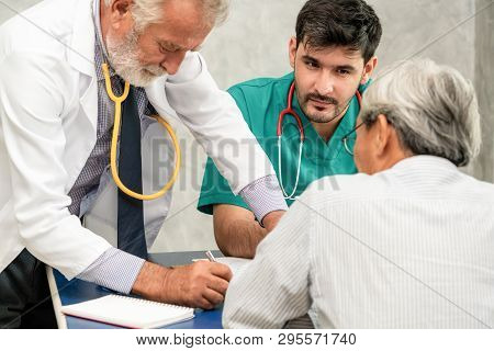 Male doctor team talking to senior patient visit at the hospital office. Medical healthcare staff service concept. stock photo