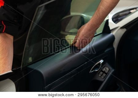 The wizard for installing additional equipment sticks a tint film on the side front glass of the car and flattens it by hand to fit the glass with a greenish tint in the auto service. stock photo
