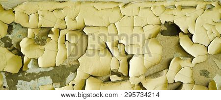 The old yellow paint peels off the wall stock photo
