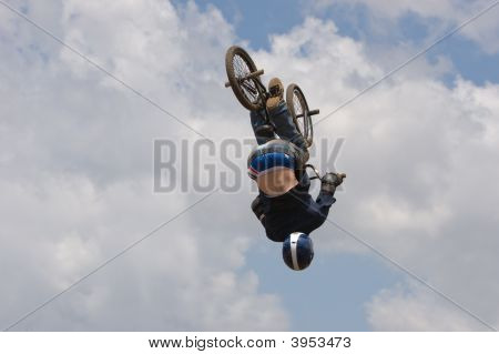 A BMX (Bicycle Moto-cross(X)) in the air upside down against the sky stock photo