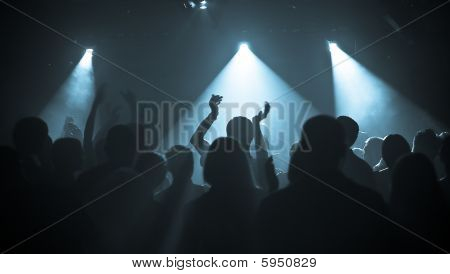 photo of hands at rock concert silhouettes against stage lighting stock photo