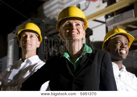 Multi ethnic office workers in storage warehouse wearing hard hats ** Note: Slight graininess, best at smaller sizes stock photo
