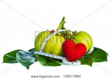 Garcinia atroviridis fruit with measuring tape and red heart-shaped on leavesisolated on white background. Herb sour flavor lots of vitamin C for good health. Diet healthcare weight reduction concept stock photo