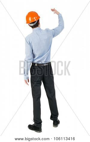 Backview of an engineer in construction helmet stands. Standing young guy. Rear view people collecti