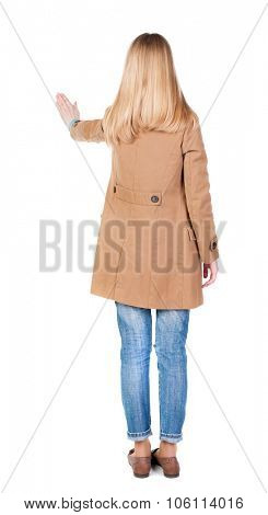 back view of woman. Young woman in cloak presses down on something. Isolated over white background.