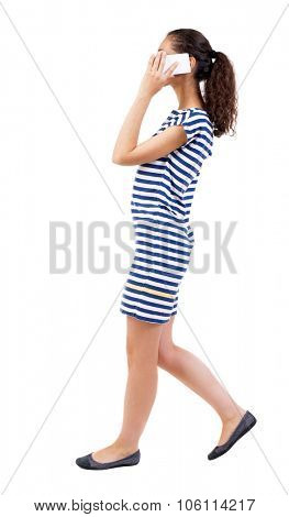 a side view of a woman walking with a mobile phone. beautiful curly girl in motion.  backside view o