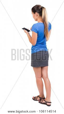 back view of standing young beautiful  woman  in vest and using a mobile phone. girl  watching. Rear