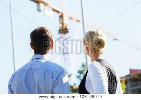 Business people looking at crane, Economics, real estate and construction concept.