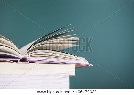 School books on desk education concept  on the Green background