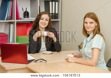 Two Employees Of The Office Drinking Tea