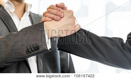 Close Up Of Two Businessmen In Gray Business Suit Gripping Their Hands In Success