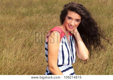 Outdoor portrait of a young beautiful woman smiling to the camera.