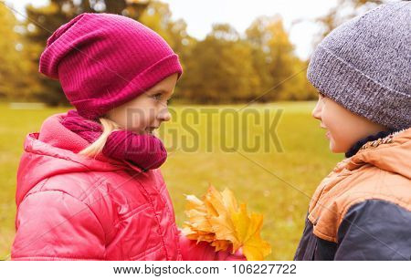 childhood, leisure, friendship and people concept - happy little boy giving maple leaves to girl in