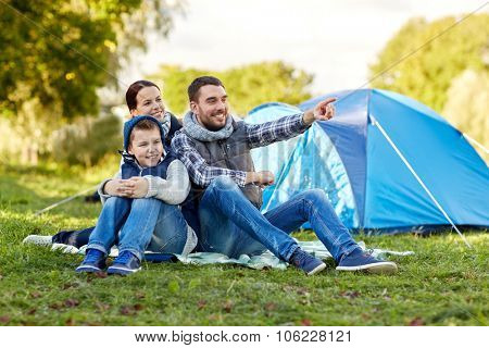 camping, tourism, hike and people concept - happy family over tent at camp site pointing finger to s