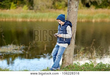 people, children and technology concept - happy teenage boy playing game or texting message on smart