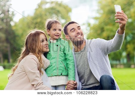 family, childhood, technology and people concept - happy father, mother and little daughter taking s
