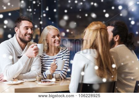 people, leisure, communication, season and concept - happy friends meeting and drinking tea or coffe