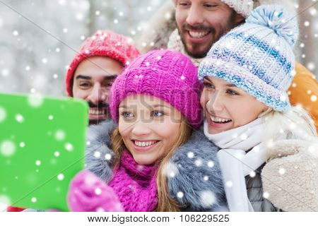 technology, season, friendship and people concept - group of smiling men and women taking selfie tab