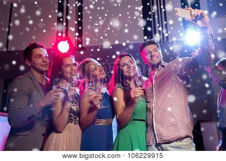 new year party, holidays, technology, nightlife and people concept - smiling friends with glasses of